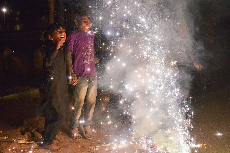 This photo taken on November 7, 2018 shows Indian children watching firecrackers during the Diwali Festival celebrations in Ajmer, in western Rajasthan state. - Diwali, the Festival of Lights, marks victory over evil and commemorates the time when Hindu god Lord Rama achieved victory over Ravana and returned to his kingdom Ayodhya. (Photo by Shaukat Ahmed / AFP)
