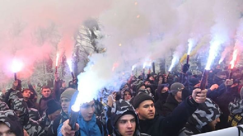 Ukrainian far-right activists hold flares during their rally, seeking a martial law in the country and cutting diplomatic ties with Russia, outside the Ukrainian Parliament in Kiev on Monday.—AFP