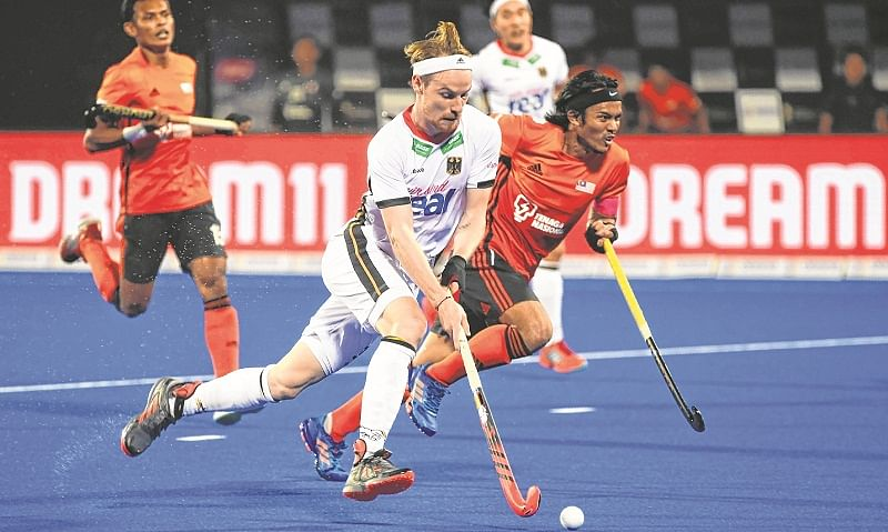 Germany's Christopher Ruhr (C) fights for the ball with Malaysia's Sukri Mutalib during the field hockey group stage match between Germany and Malaysia at the 2018 Hockey World Cup in Bhubaneswar on December 9, 2018. (Photo by Dibyangshu SARKAR / AFP)