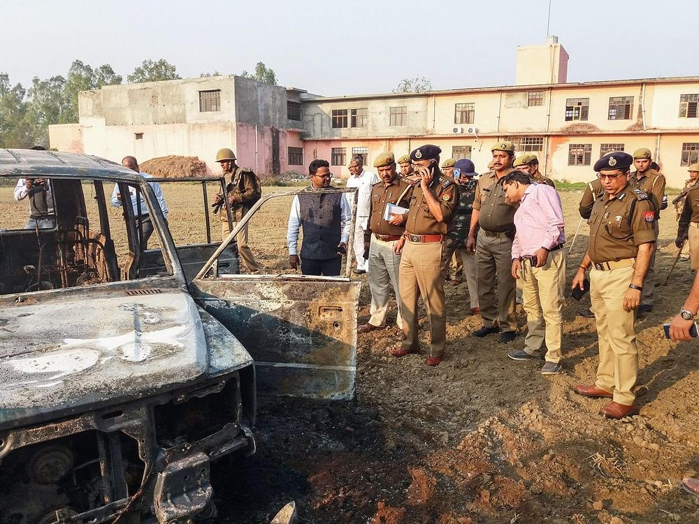 Bulandshahr: Policemen inspect after several vehicles were set on fire by a mob during a protest over the alleged illegal slaughter of cattle, in Bulandshahr, Monday, Dec. 03, 2018.  According to Additional Director General of Meerut zone Prashant Kumar, protesters from Mahaw village and nearby areas pelted stones on the police and indulged in arson setting several vehicles and the Chingarwathi Police Chowki on fire. (PTI Photo)(PTI12_3_2018_000216B)