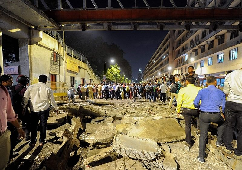 Onlookers and office goers gather around rubbles of a footbridge outside the Chattrapati Shivaji Maharaj Terminus railway complex in Mumbai on March 14, 2019. - Four people were killed and dozens injured when a footbridge collapsed near Mumbai's main train station on March 14, the latest accident to highlight creaking infrastructure in India's financial capital. (Photo by STR / AFP)