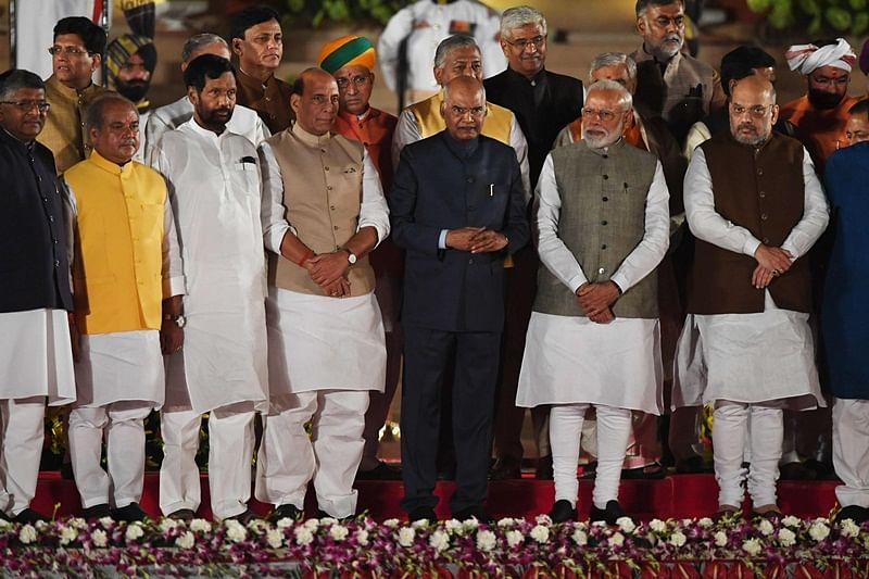 Newly sworn-in Indian Prime Minister Narendra Modi (2R) and cabinet ministers stand with President of India Ram Nath Kovind (C) after taking the oath of office at the President house in New Delhi on May 30, 2019. - India's Prime Minister Narendra Modi was sworn in Thursday in front of cheering supporters ahead of unveiling a drastically revamped Hindu nationalist government for his historic second term. Modi was the first of more than 50 cabinet ministers and deputy ministers to take the oath of office at the presidential palace in front of 8,000 people including South Asian leaders, Bollywood stars and leading political figures. (Photo by PRAKASH SINGH / AFP)