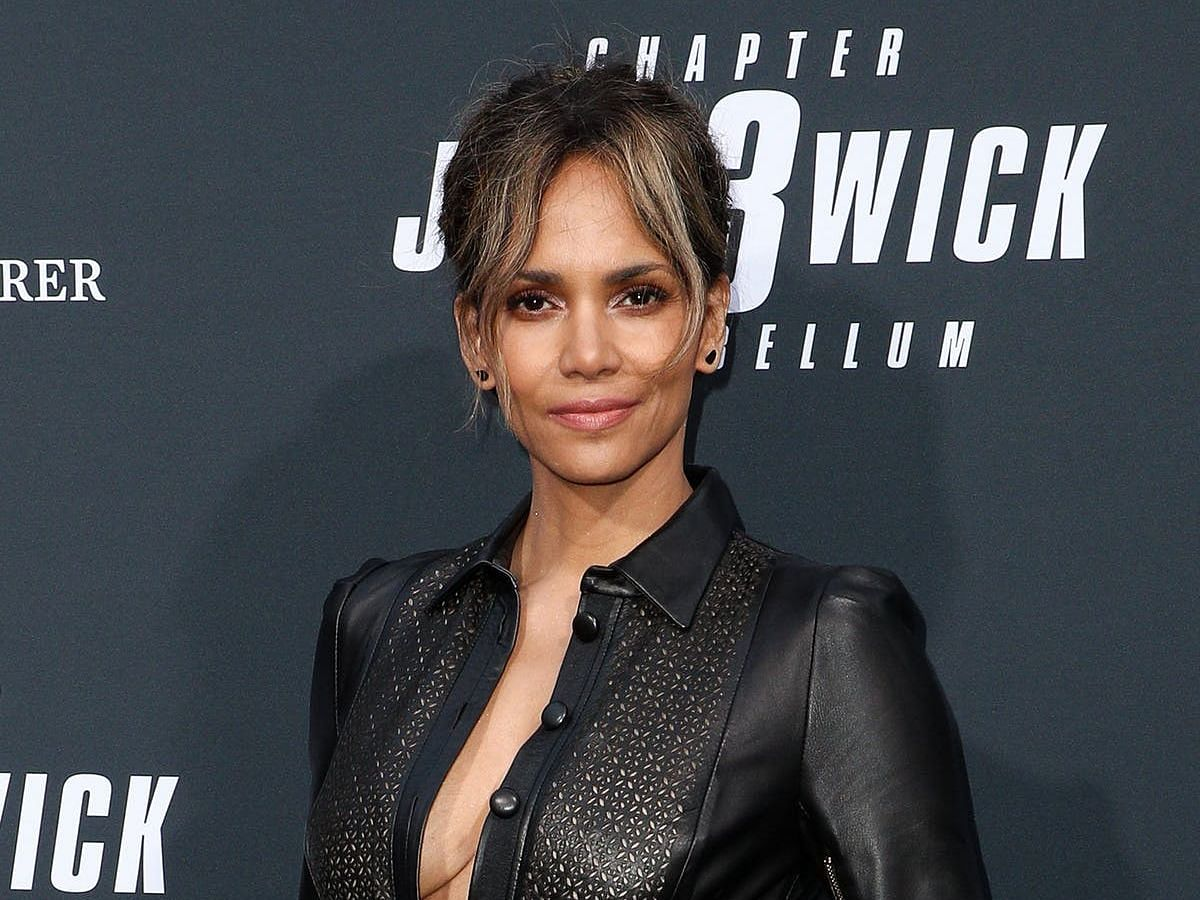 Halle Berry poses at a movie premiere, wearing a black collared shirt and her hair pulled back