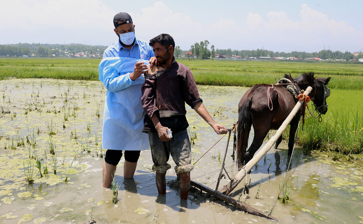 A farmer gets his first dose of COVID-19 vaccine as he ploughs his field, on Saturday 5 June 2021.