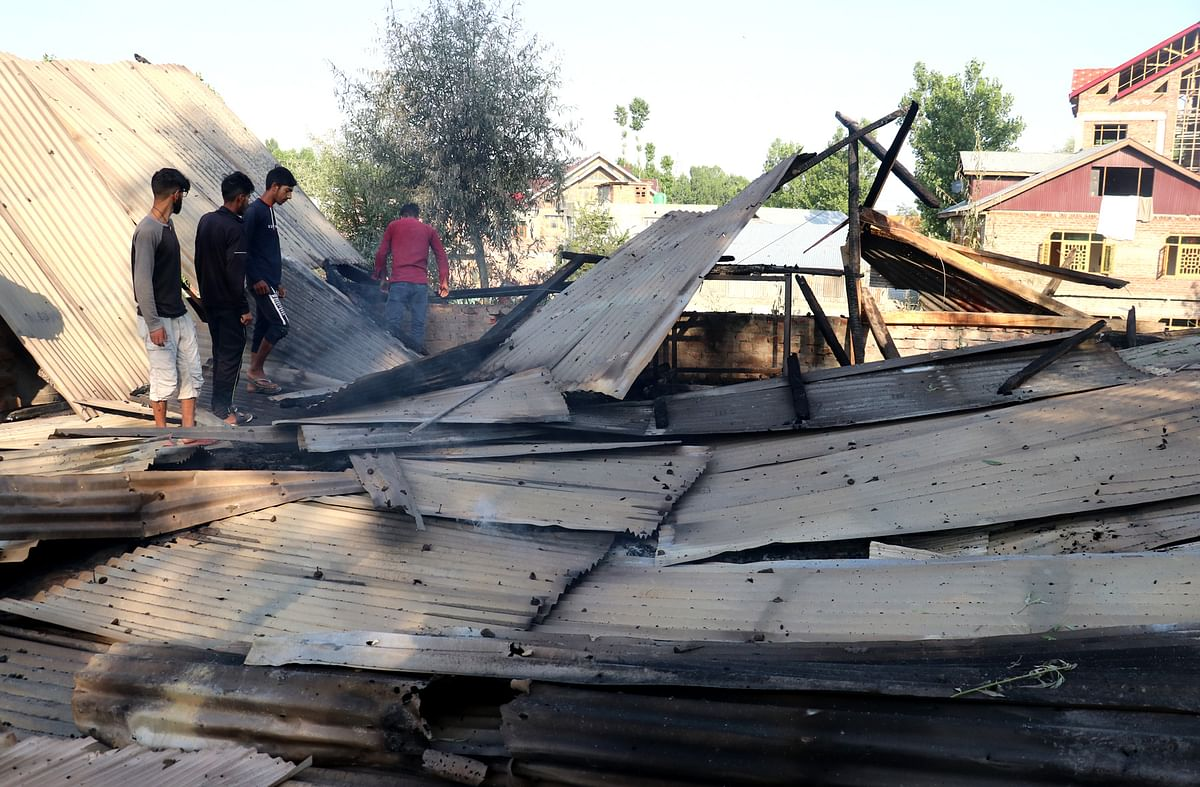 Locals clear the debris of a house which was brought down during a gunfight, on Tuesday 29 June 2021.