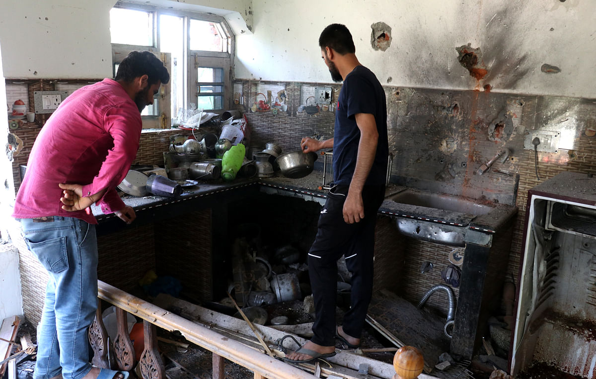 Residents assess the damages caused to the house in which the slain militant had taken cover during a gunfight with the security forces, on Tuesday 29 June 2021.
