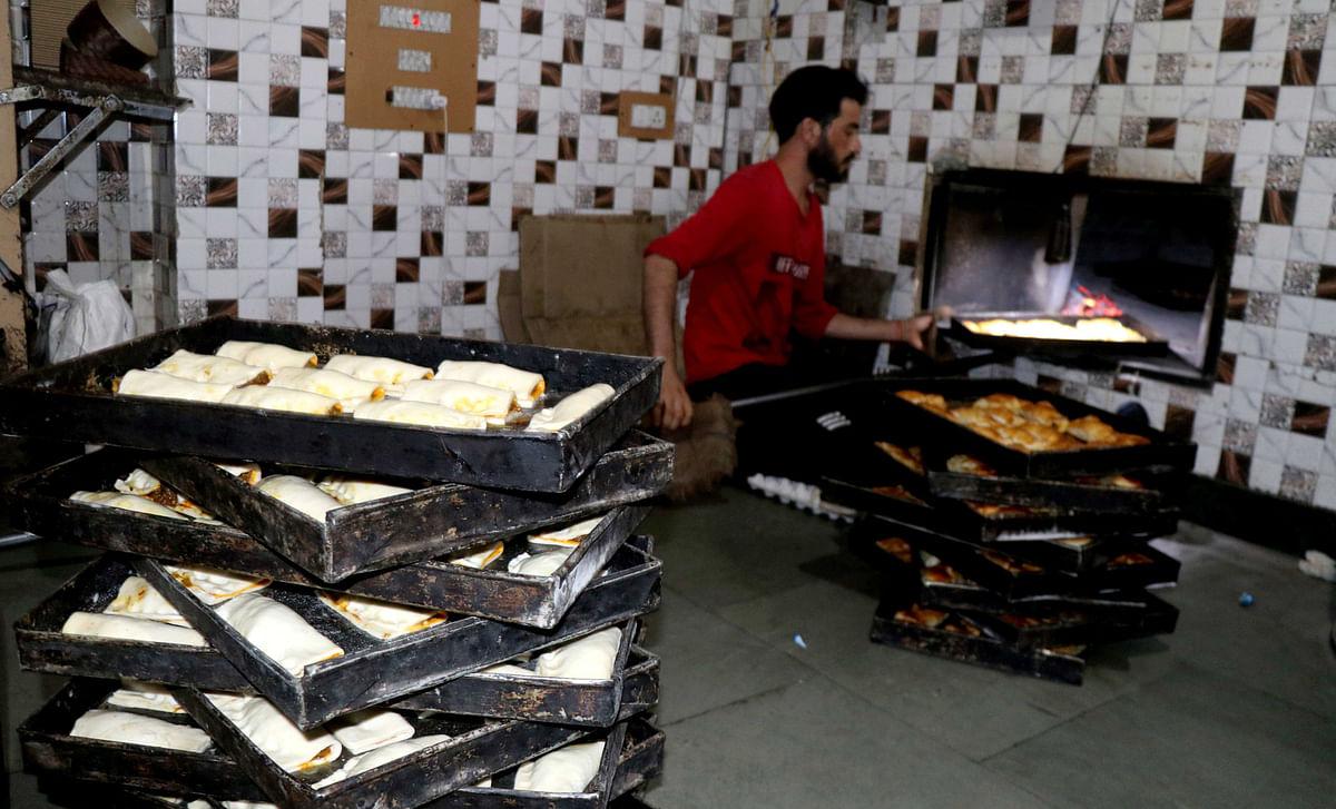 A baker prepares bakery at his shop in Srinagar ahead of Eid-ul-Adha.