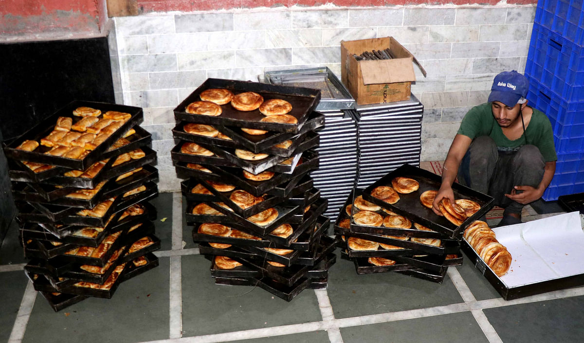 A baker sorts out bakery at his shop in Srinagar ahead of Eid-ul-Adha.