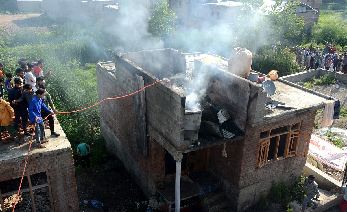 Locals try to douse the flames after the gunfight ended in Eidgah area.