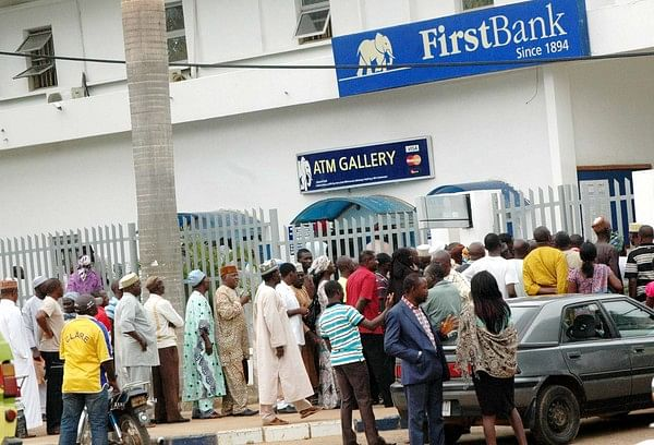 Customers waiting on a queue outside a bank to use the ATM