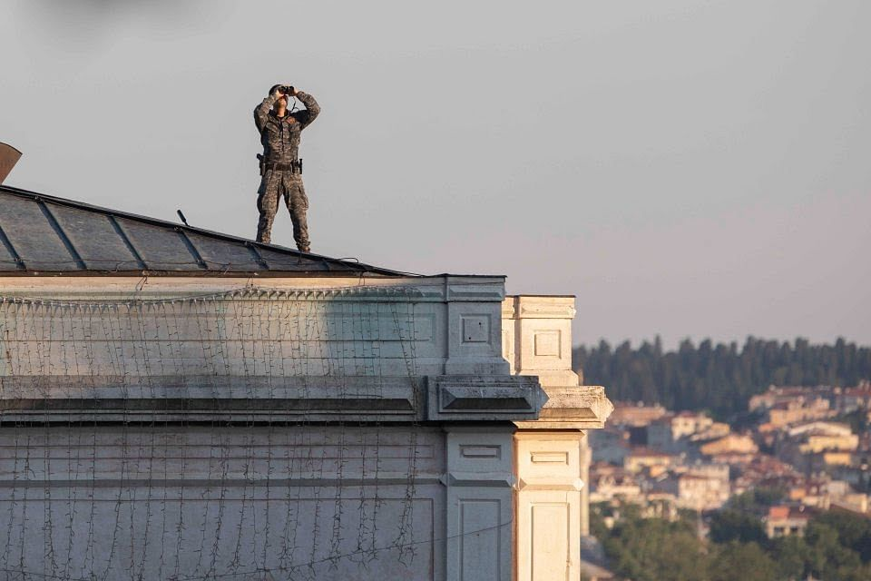 A soldier at the roof doing routine check