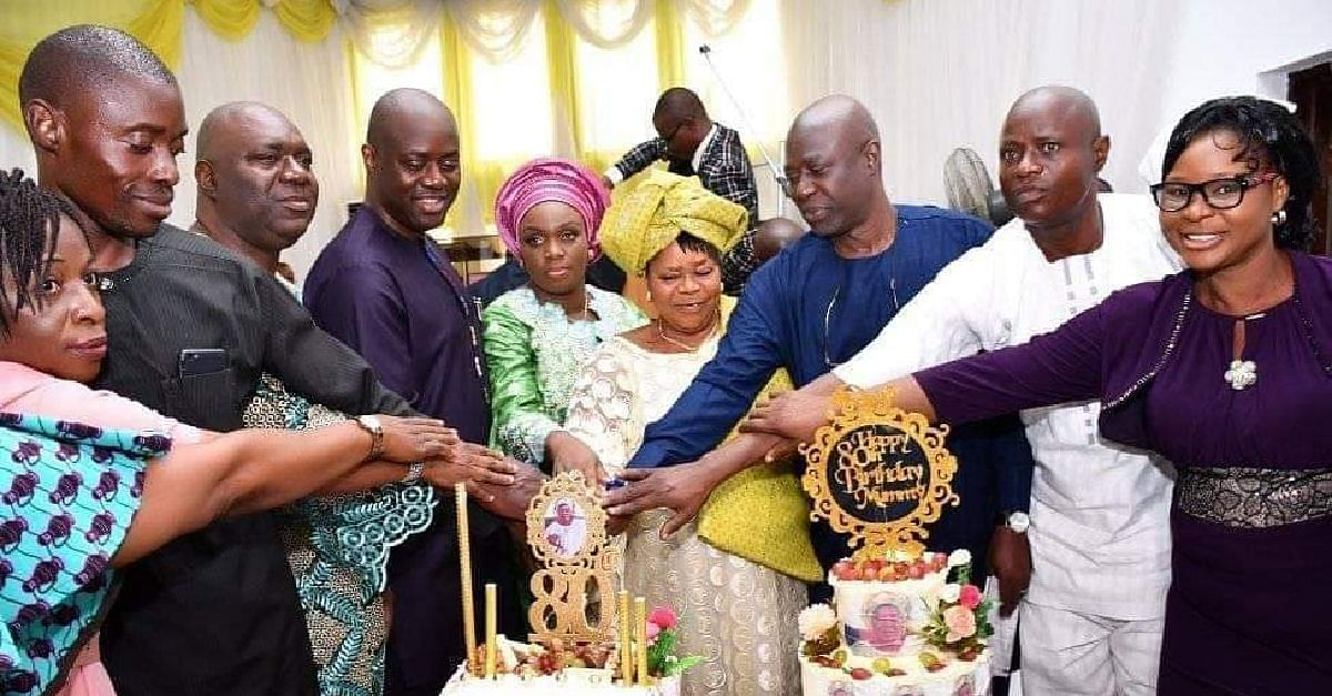 Makinde, mother and family members cutting the cake