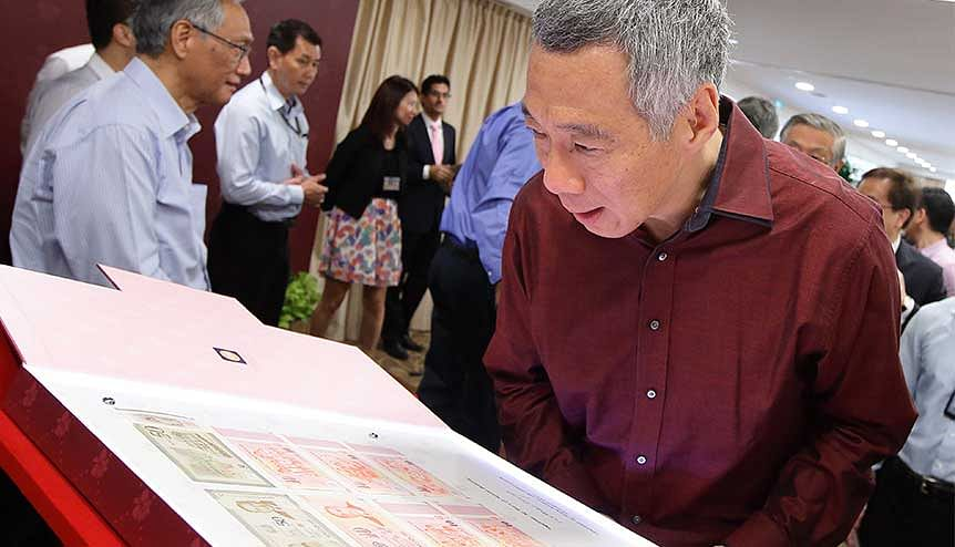 Singapore's PM Lee Hsien Loong looks at commemorative currency notes. Monetary Authority of Singapore (MAS) issued digital-only banking licenses to empower the integration of fintech and banking in a fast-paced digital economy.