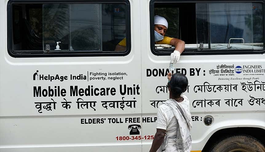 Elderly woman receives medicine from a health worker sitting inside a mobile medicare van. The pandemic has driven demand for health insurance.