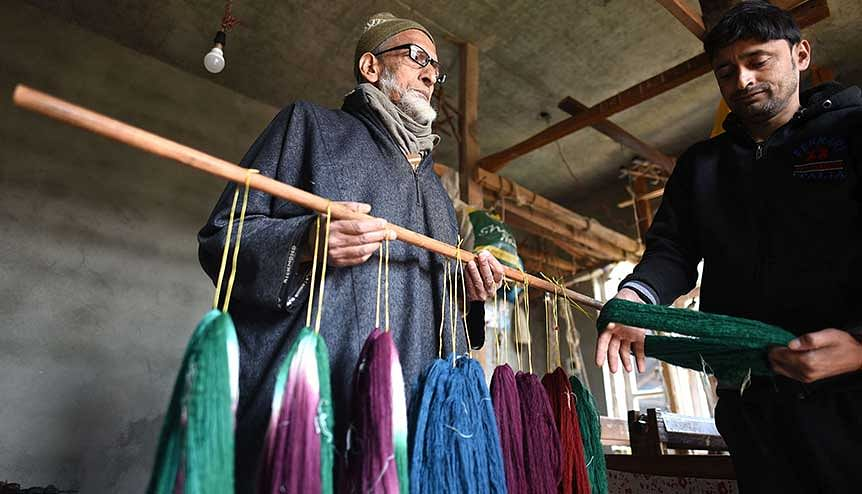 A Kashmiri artisan is seen checking the dyed yarn during the weaving process of Pashmina shawl inside a workshop at his residence. This handicraft has received industry status along with other small-scale and cottage industries.