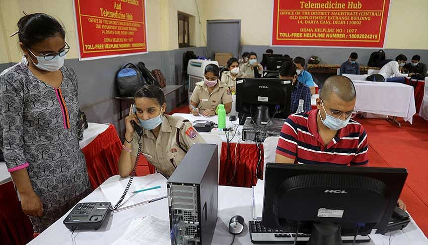 Indian volunteers from Delhi Civil Defence (DCD)work at the Covid-19 District Central Surveillance and Tele-medicine Hub to serve as a free helpline service for the COVID-19 patients and their families.