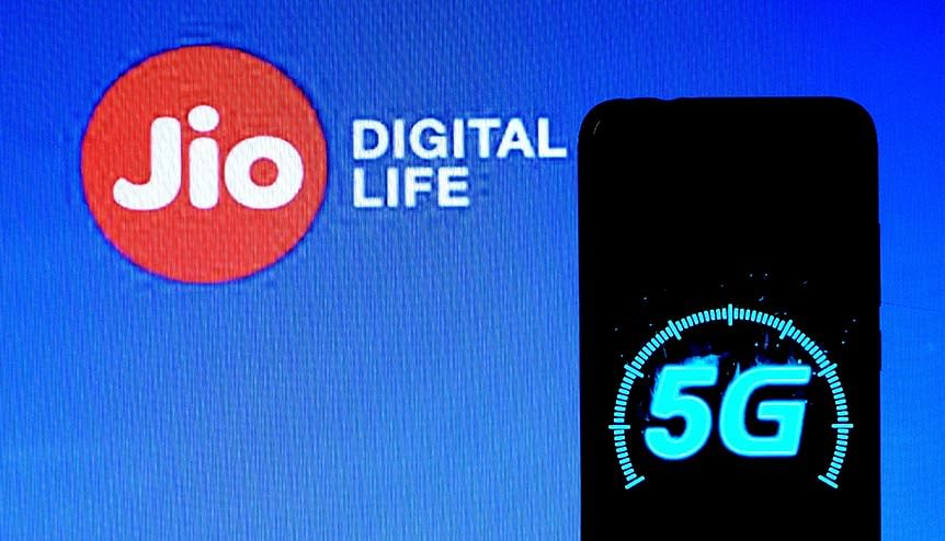 A 5g mobile Spectrum logo displayed on a smartphone with a Jio Digital life logo in the background. Indian companies are investing increasingly in tech infrastructure.