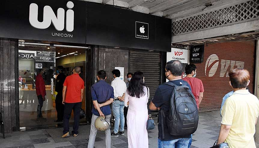 Customers stand in a queue while purchasing mobile phones at a shop at Hazratganj Market during lockdown. Market analysts are predicting bumper festive season sales for e-commerce this season.