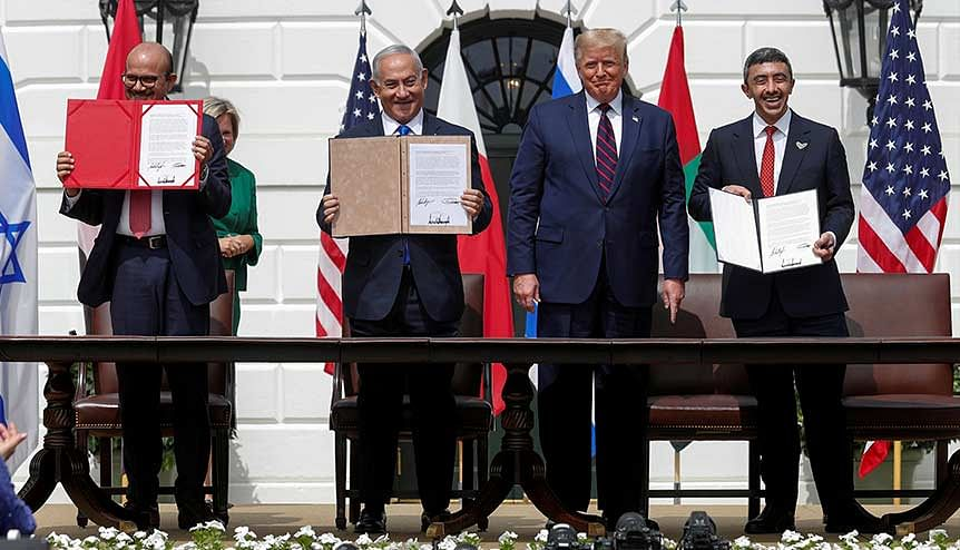 Bahrain's Foreign Minister Abdullatif Al Zayani, Israel′s Prime Minister Benjamin Netanyahu and United Arab Emirates (UAE) Foreign Minister Abdullah bin Zayed display their copies of signed agreements as they participate in the signing ceremony of the Abraham Accords.