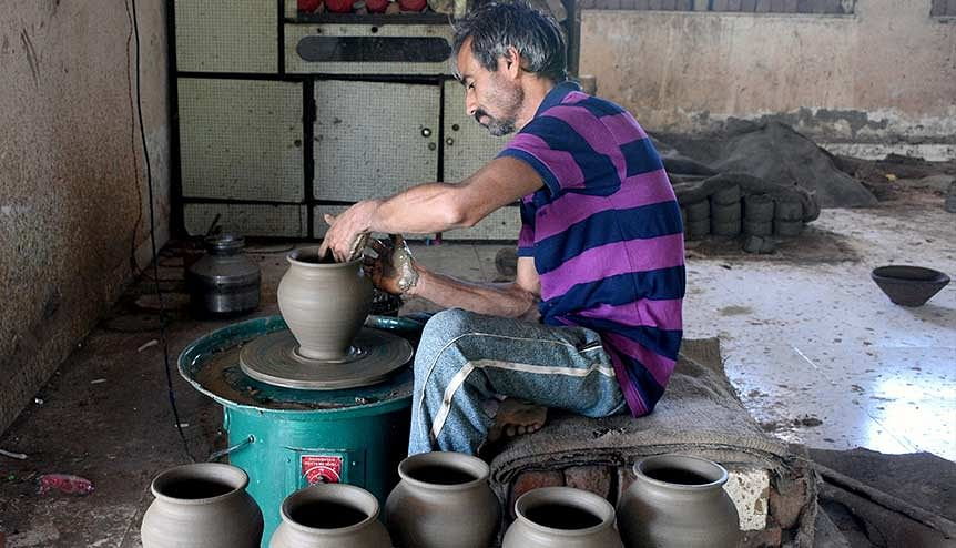 Just a glimpse of Gujarat's pioneering spirit. A potter making clay pot lamps in Surat. If Gujarat were a country with a 10 million-plus population, it would boast the third-fastest growth rate in the world on average.