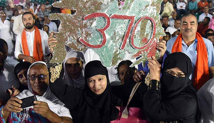 Muslim women hold a placard during the Jan Jagran program on Article 370. the far Left of the Democratic Party has been critical of India for enacting legislations such as Article 370 and the CAA.