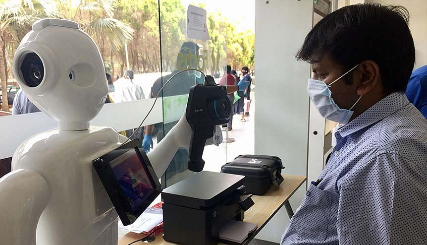 A robot at Fortis hospital in Bengaluru checking a man before he enters. AI in healthcare and digital health are rapidly driving growth of the healthcare and pharmaceutical sectors in India.