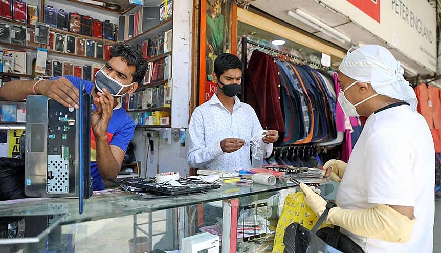 A shopkeeper repairs a customer's laptop. The government has announced fresh PLI schemes to 12 sectors. The newly announced PLI schemes by the government includes telecom and network equipment makers, pharmaceuticals and IT hardware such as laptops, tablets, PCs and servers.