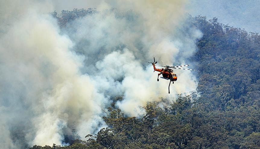 Helicopter returning to refill during water bombing out of control fires in the Jamison Valley, Blue Mountains, Australia. World over, countries have paid over $71 billion, over 95 per cent over loss and destruction caused by weather-related disasters.