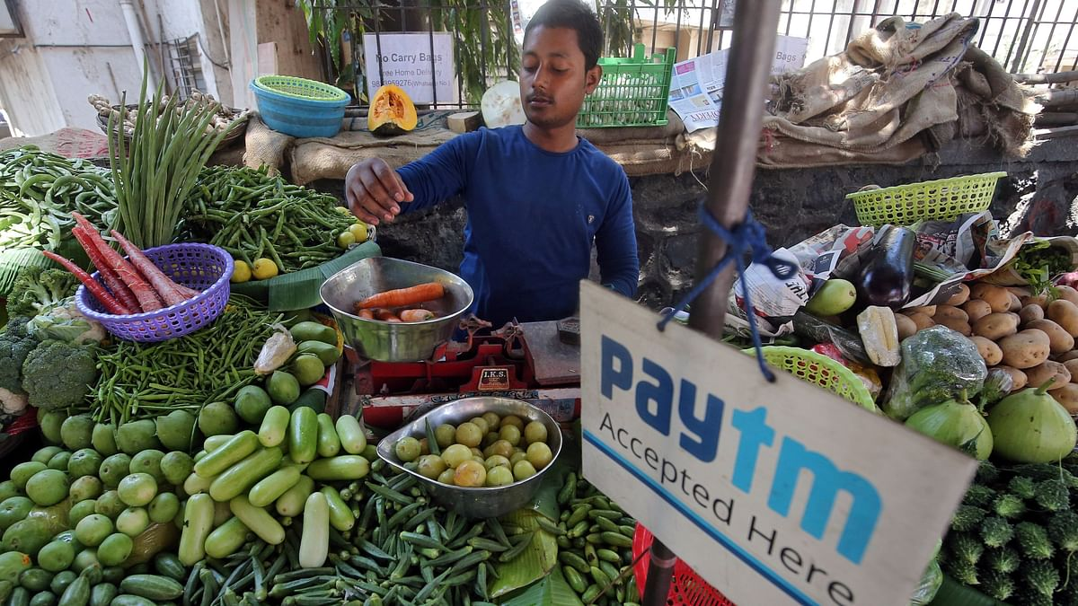 A vendor weighs vegetables next to an advertisement of Paytm, a digital payments firm in India. With nearly $50 billion raised in total in disclosed funding rounds, more than 15 unicorns have come up in India in the past two years, thanks to the rapid rise of the consumer market as well as the increasing adoption of digital services.