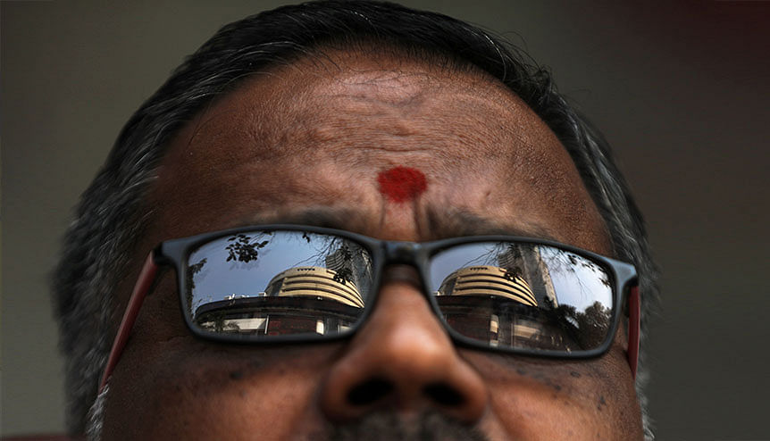 The Bombay Stock Exchange (BSE) building is reflected in the glasses of a man as he watches a large screen outside the facade of the building. Mammoth FDI's into India has ensured that the country is within striking distance of its target to secure $100 billion FDI annually.