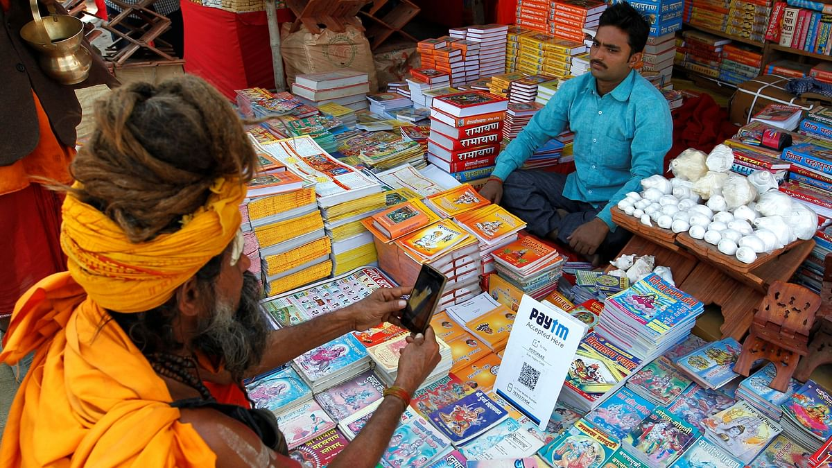 A Sadhu or a Hindu ascetic pays the vendor through Paytm, a digital wallet company, after buying a book during the annual religious festival of Magh Mela. Of the more than 2,100 fintech companies that operate in India currently, 67% have been set up in the past five years.