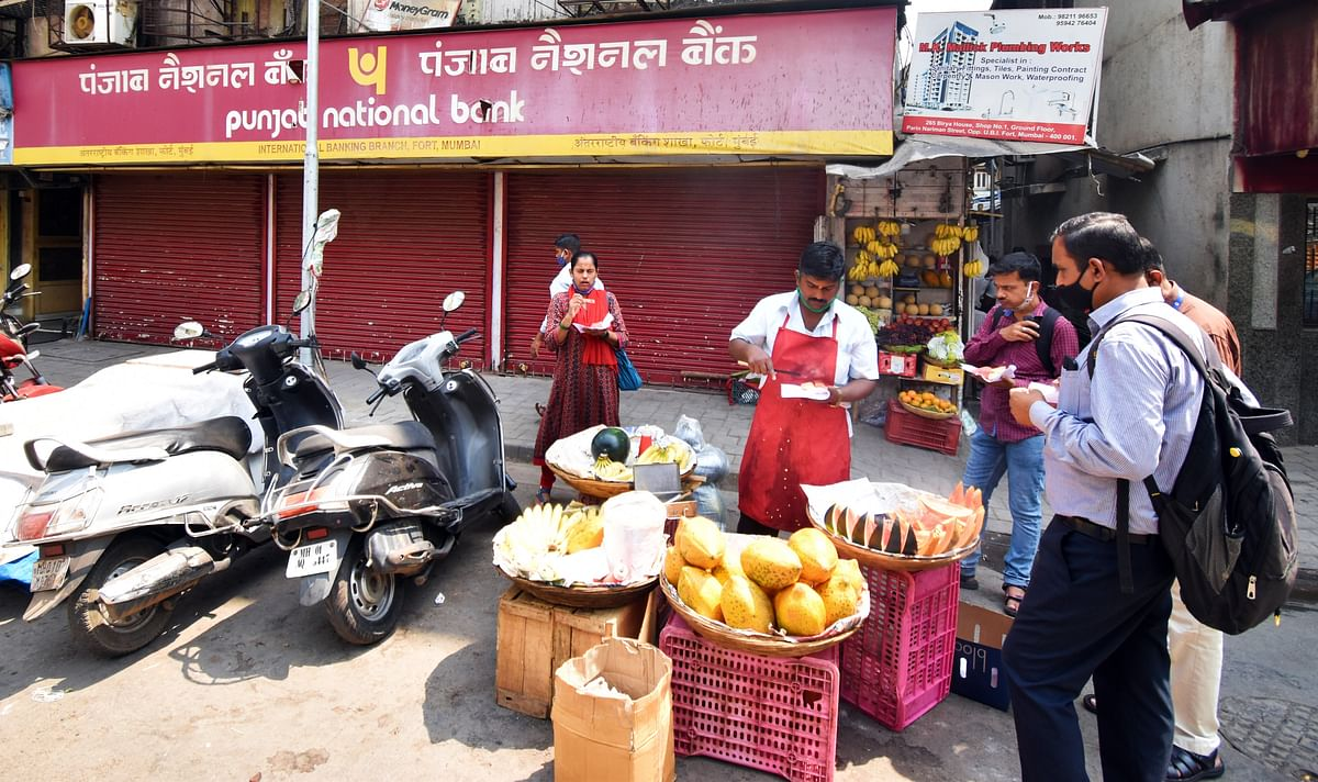 People eating fruit at a street side stall in Mumbai against the backdrop of a closed PNB Bank. Maharashtra has emerged with a positivity rate of 16%.