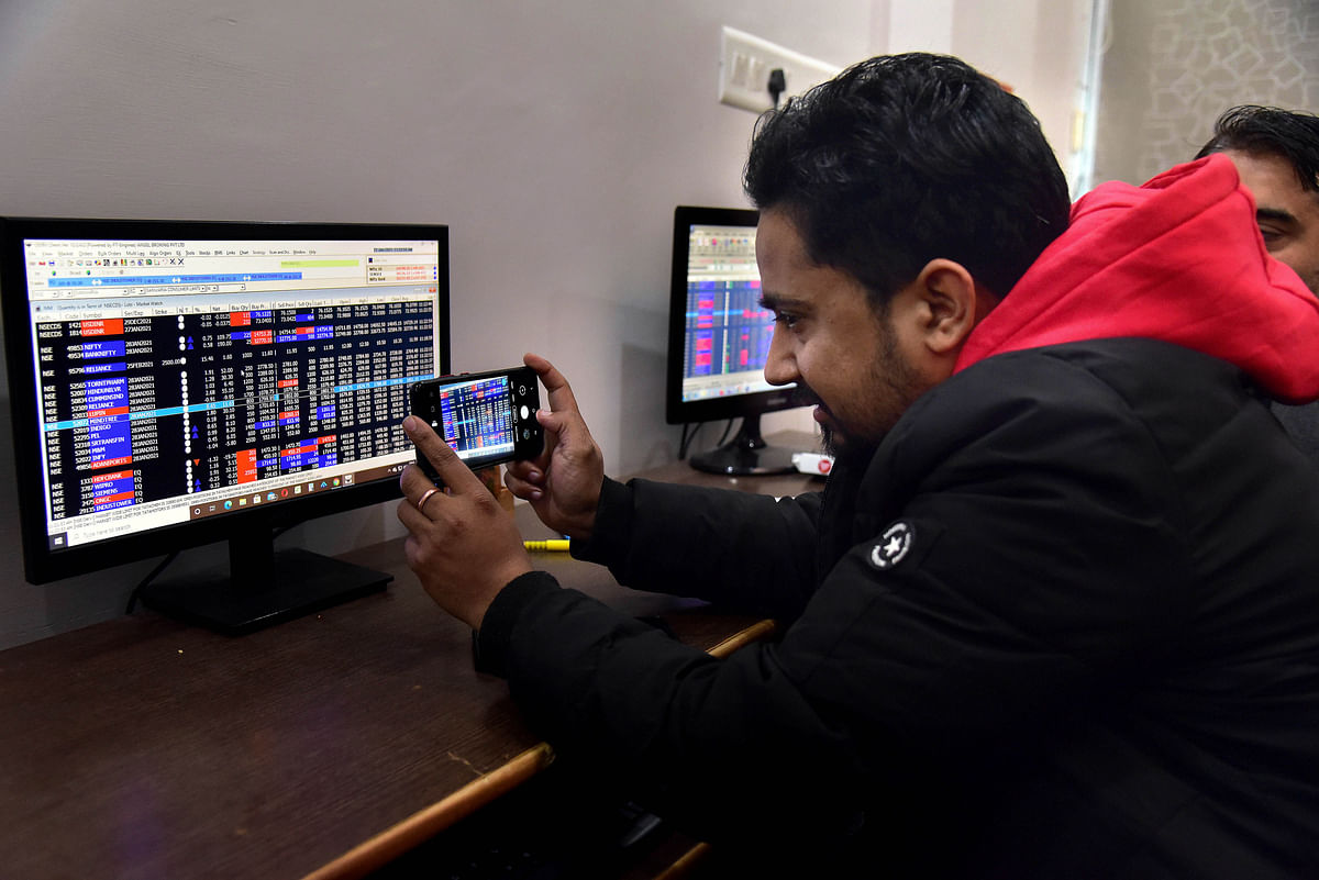 A broker takes a photo of the days results on the stock market. India's foreign exchange reserves, which had touched a record high of $590.19 billion in the week ended January 29, 2021 before dipping slightly to their current levels, are now sufficient to cover one year's worth of imports.