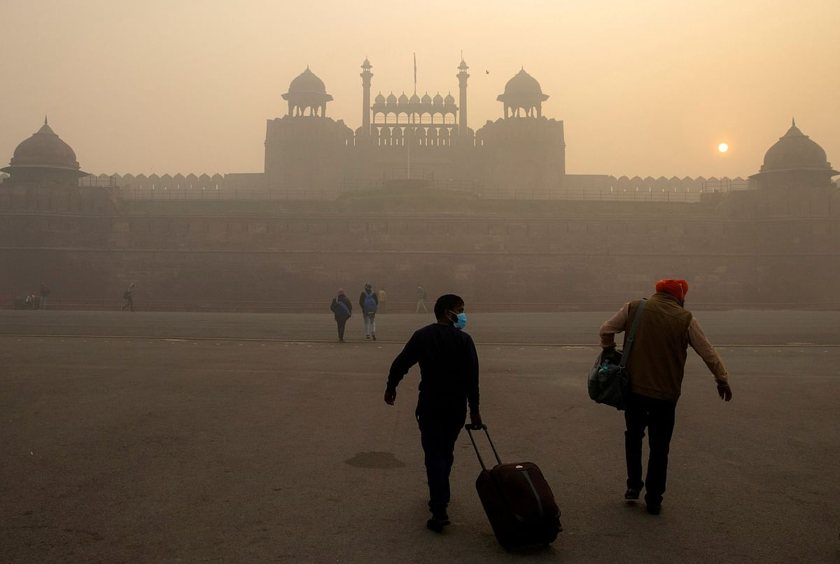 People arrive to visit the Red Fort on a smoggy morning in the old quarters of Delhi, India. Nearly $84.4 billion of debt at India's leading financial institutions was at risk from extreme weather events such as droughts, floods and cyclones.