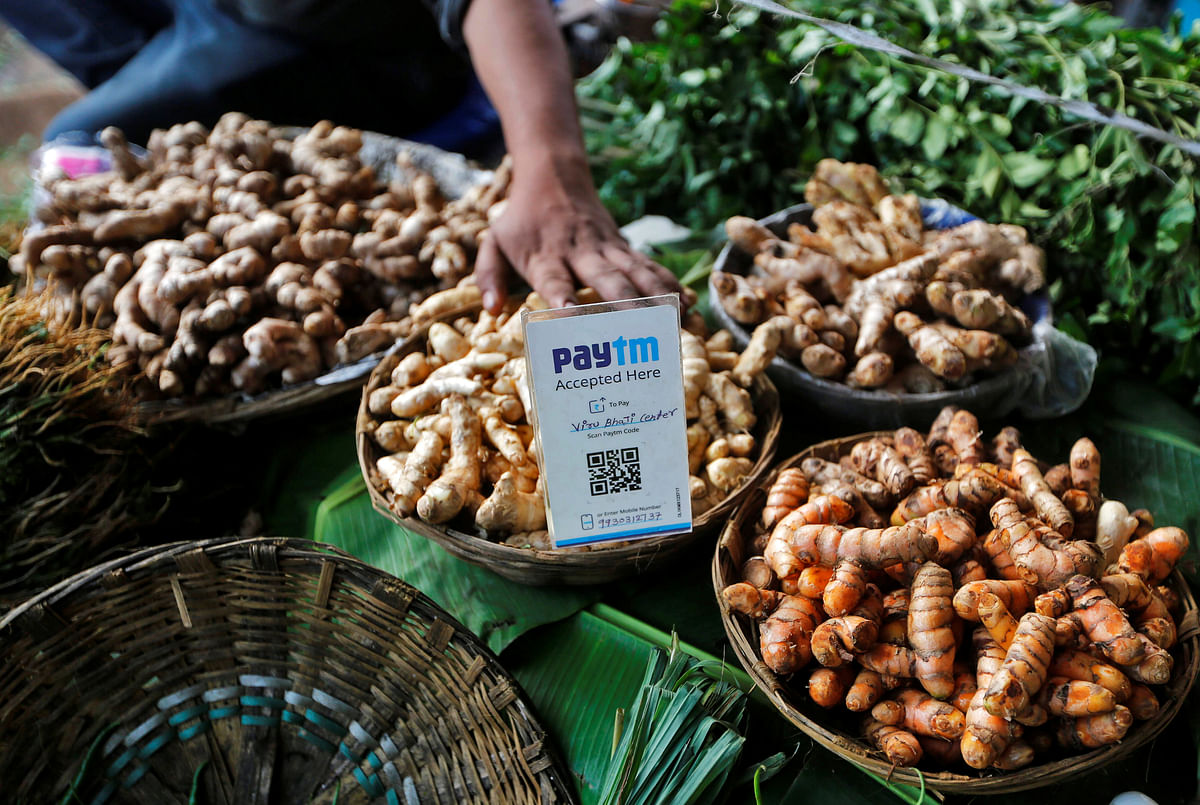 An advertisement board displaying a QR code for Paytm, a digital wallet company, is seen placed amidst vegetables at a roadside vendor's stall. Revolut's launch in India has been pegged as the latest step in its international expansion plans, following successful launches in Singapore and Australia in 2019, and the US and Japan in 2020.