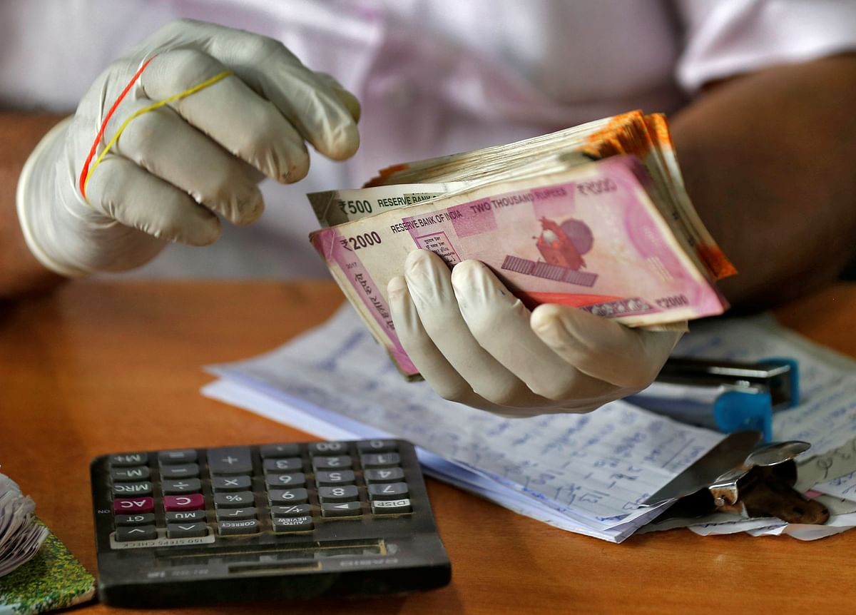 A trader wearing protective hand gloves counts Indian currency  at a market. Revolut is looking at the way people in India access and manage their money.