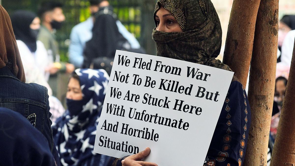 Afghanistan refugee families hold a placard during a protest demanding their basic rights. The Taliban are primed to take over the country when foreign  troops withdraw.