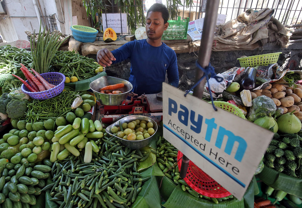 A vendor weighs vegetable next to an advertisement of Paytm, a digital payments platform. The government's relentless efforts to push for the adoption of digital payments methods over cash transactions is paying off.