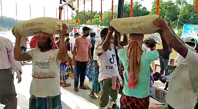 Workers unloading cement from vessels as the First trial vessel with cement from Bangladesh reached Sonamura port. Thanks to the government's housing programme demand for cement will rise by 20 percent in the current fiscal.
