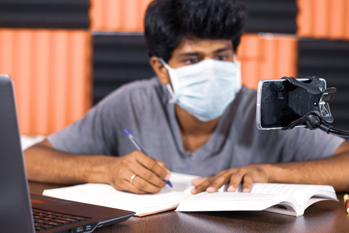 A college student taking notes by looking into virtual class on mobile due to quarantine. India is favourably placed to reap the benefits of digitalization of education that will fundamentally transform how the country learns.