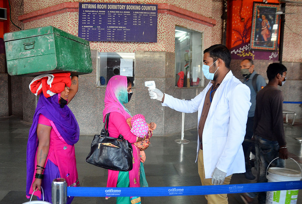 A healthcare worker checks the temperature of a passenger who arrived at Charbagh Railway Station in Lucknow. Rural India houses nearly 70% of India's 1.3 billion people.