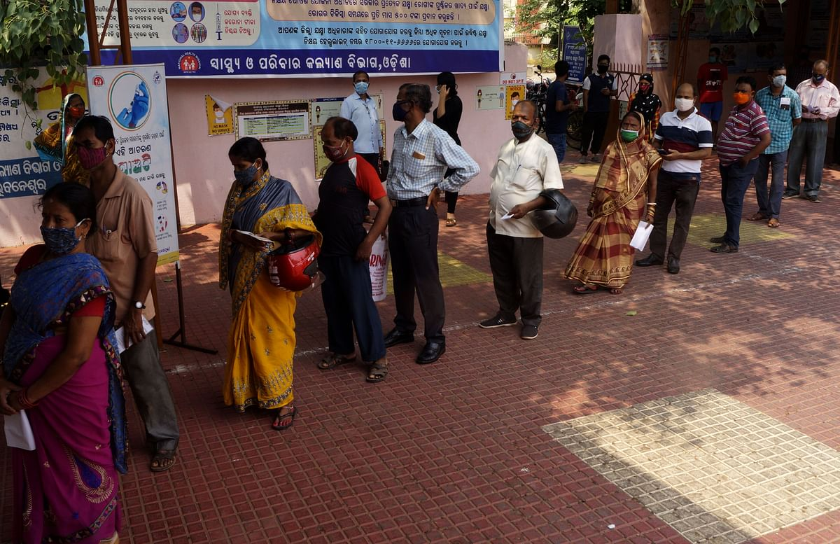 People queue up to buy medicine. According to Fitch Ratings, sales for drug makers in the near term will be boosted by demand for Covid-19 related drugs, particularly in India.