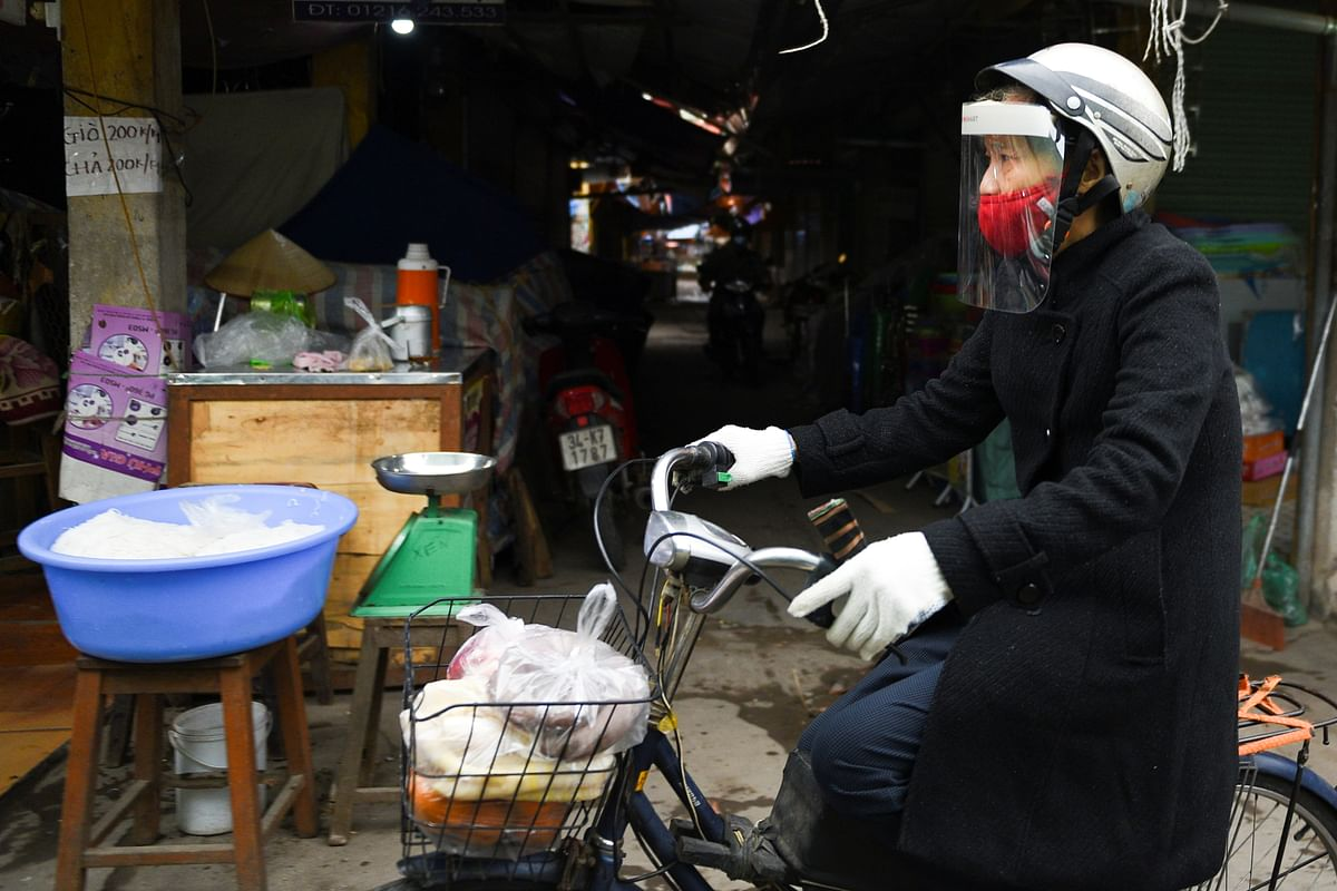 A woman wears a protective mask as she rides a bike at a market in Vietnam after Hai Duong authorities end 34 days of social distancing. Asia continues to be a strong engine for global FDI due to high growth numbers and due to shift in manufacturing capacity from China.