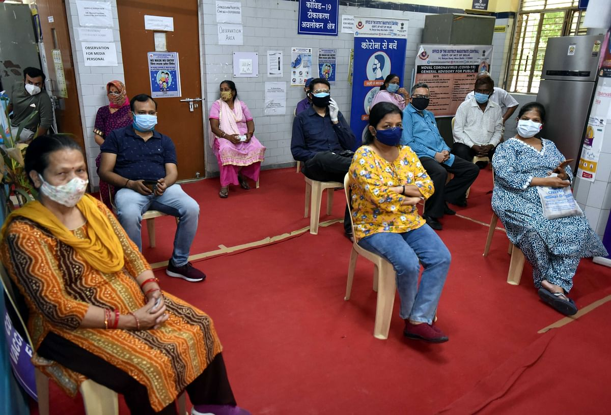 People sit in an observation room after receiving Covaxin vaccine. The risk of further waves of infection remains significant in markets with slow roll-outs of vaccination, including India, but healthcare systems are better prepared after the second wave, which should limit the impact.