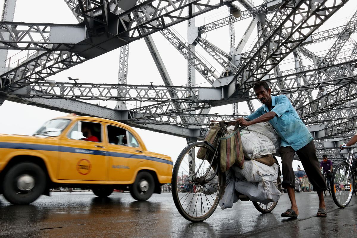 Commuters carry goods past the Howrah Bridge over the Hooghly River. Fuel prices in India have are going through regular hikes but they are not issues that can be moderated through monetary policy measures.