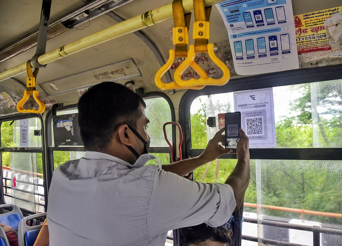 A man scans a QR code with a smartphone to buy a bus e-ticket under 3 days trial of contactless ticketing by Delhi Government. Global companies with a turnover of $1.3 billion, domestic companies with over Rs 2.5 billion turnover, and MSMEs with annual turnover of over Rs 100 million are eligible to participate in the DoT's PLI scheme.