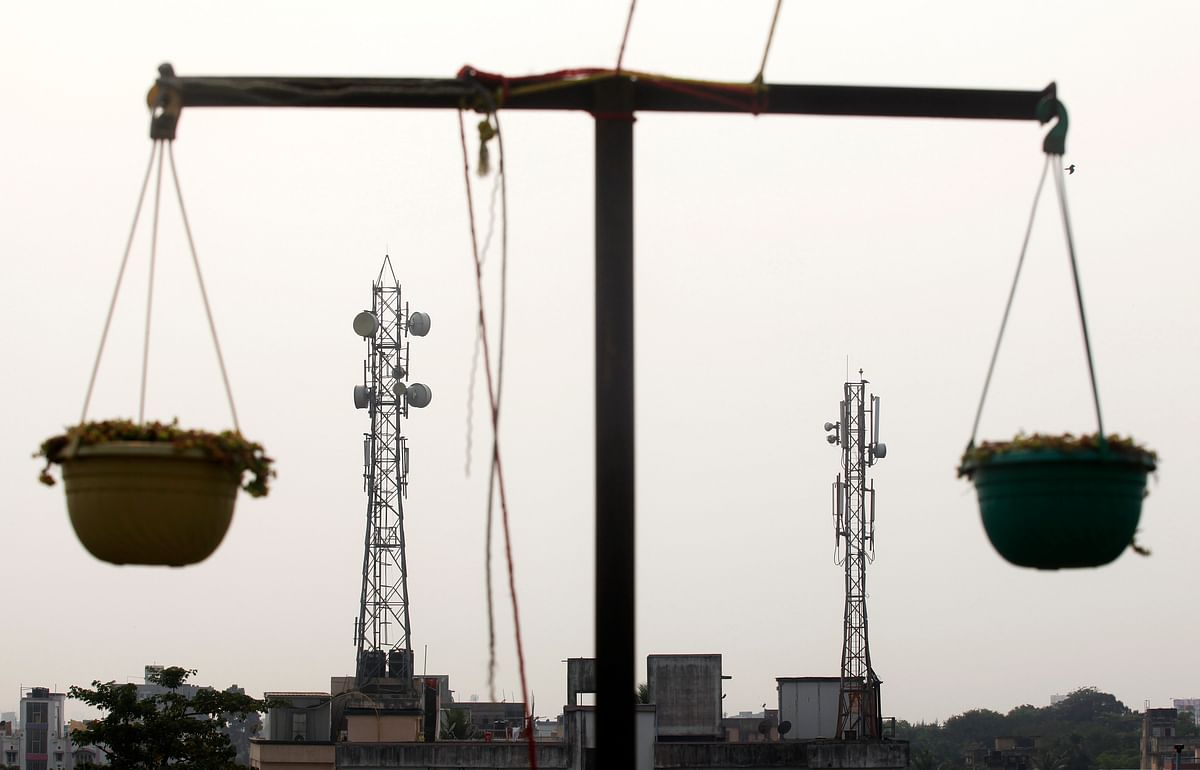 Telecommunication towers are pictured through hanging flower pots at a residential building in Kolkata. Through its PLI schemes the DoT aims to boost local production of telecom equipment, reduce dependency on imports and provide opportunity to domestic manufacturers to focus on exports as well.
