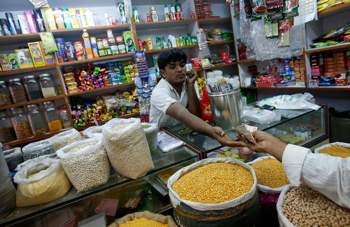 """The owner of a """"Kirana"""" or mom-and-pop grocery store goes through a transaction. The reopening of India's kirana stores is boosting demand as consumers flock to them to buy daily necessities as well as satisfy pent-up demand."""