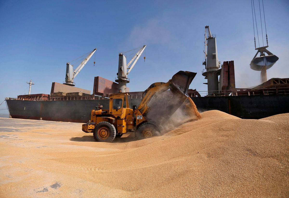 A dozer unloads wheat next to a ship at Mundra Port, one of the ports handled by India's Adani Ports and Special Economic Zone Ltd. The Group's growth model of building and developing world-class infrastructure assets and accessing global financial markets is unreplicated in India's business landscape.