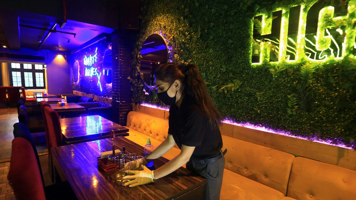 A worker arranges the glasses on the table inside High 5 bar as the Delhi government announced reopening of restaurants, in New Delhi. The future of food service remained the largest profit sector channel in 2020.